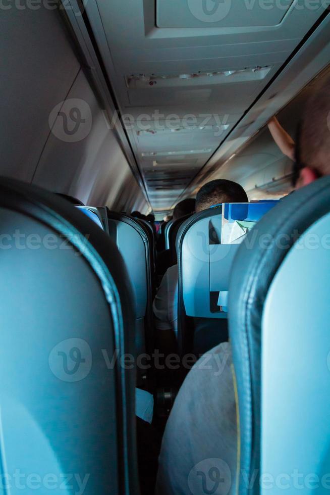 interieur van passagiersvliegtuig met mensen op stoelen foto