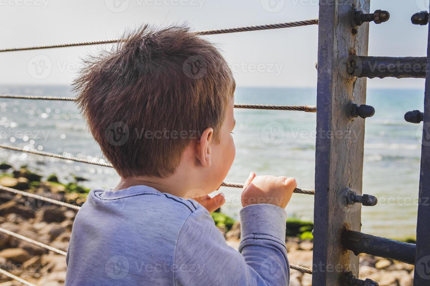 jonge jongen kijkt ver weg naar de horizon van achter een metalen hek foto