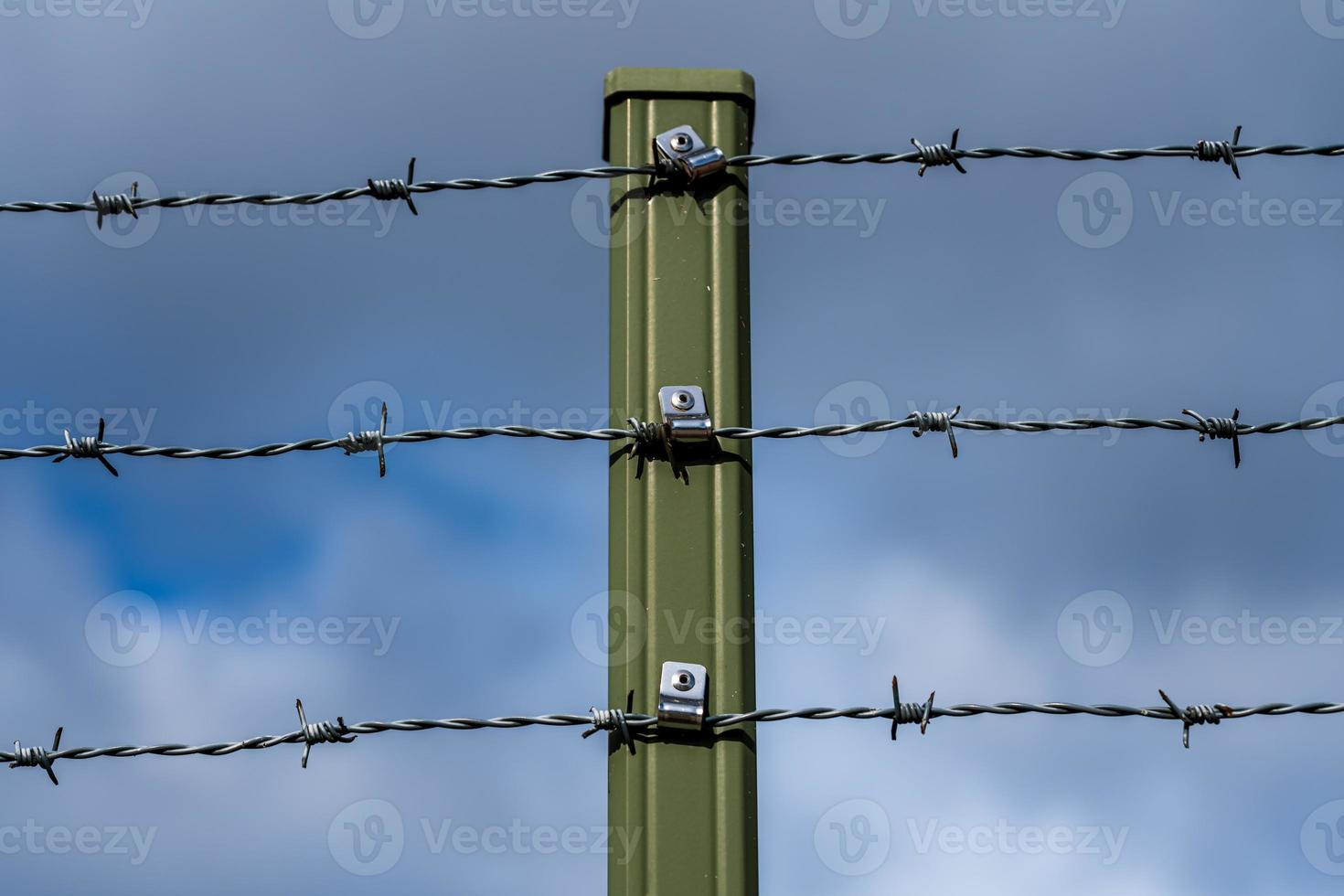 groene hekpaal met drie rijen prikkeldraad foto