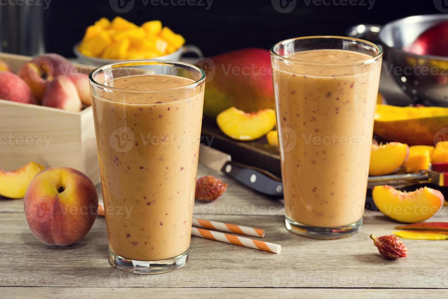 twee smoothies van perzikmango in glazen met ingrediënten foto