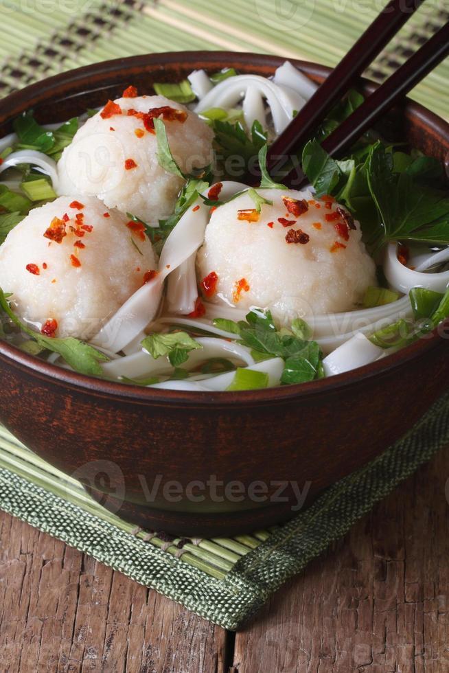 rijst noodlesoep met visballetjes in kom close-up. verticaal foto