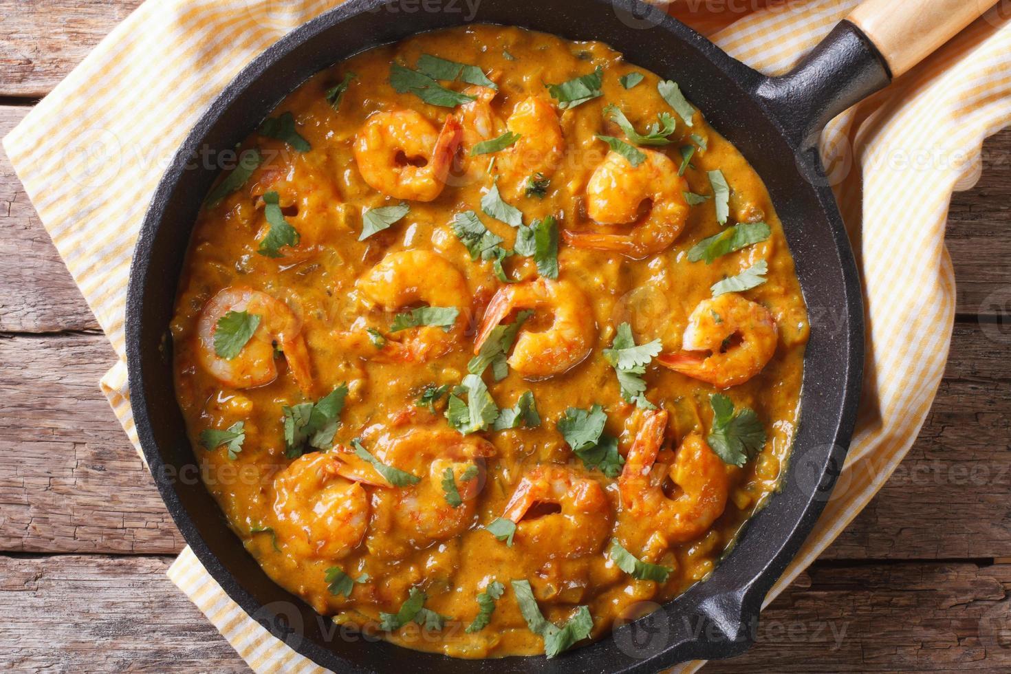 garnalen in currysaus in pan close-up horizontale bovenaanzicht foto