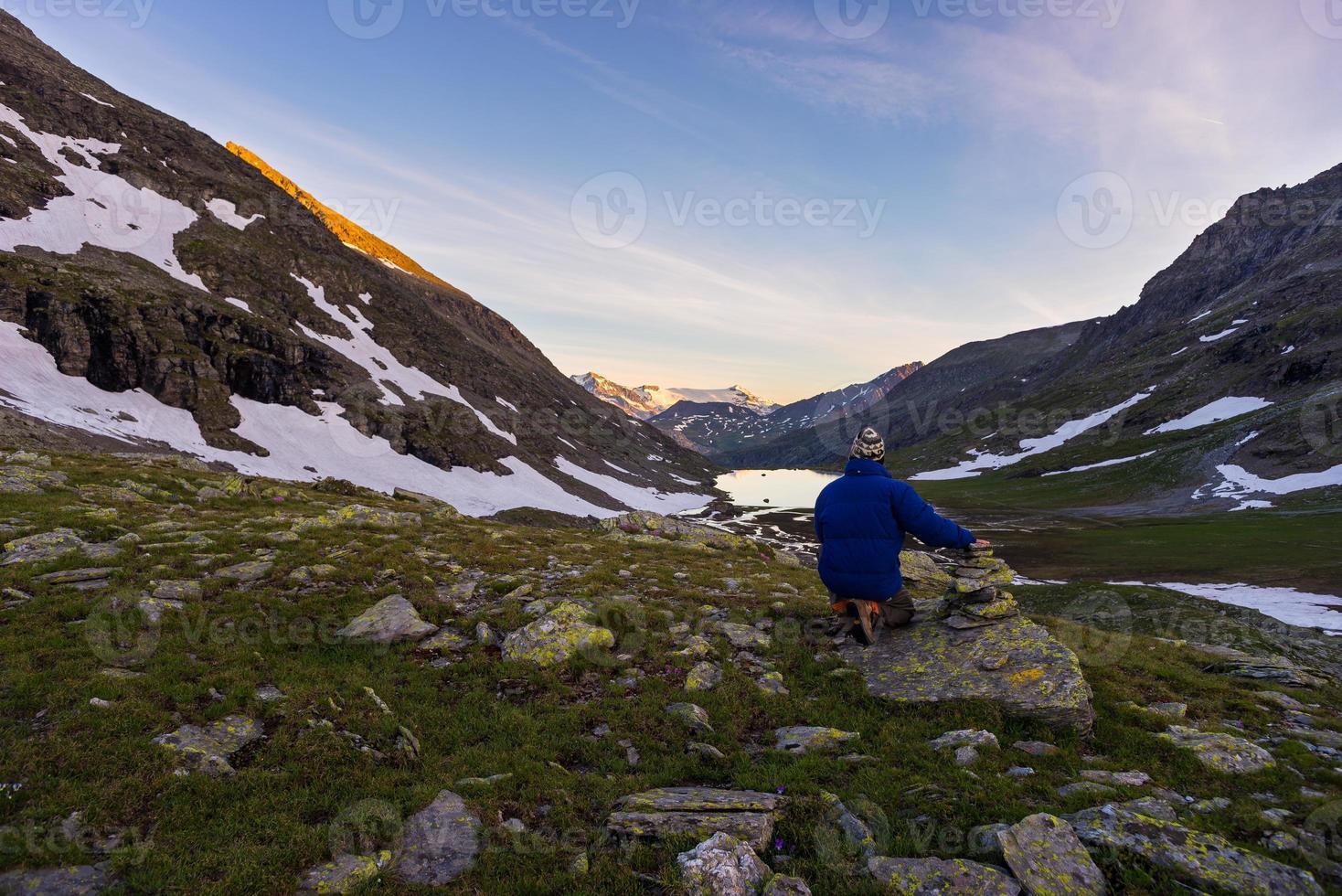 een persoon die zonsopgang hoog in de Alpen bekijkt foto