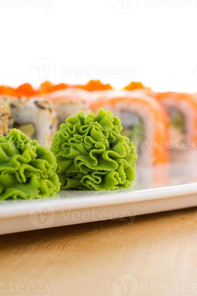 sushi ingesteld op witte plaat op houten achtergrond foto