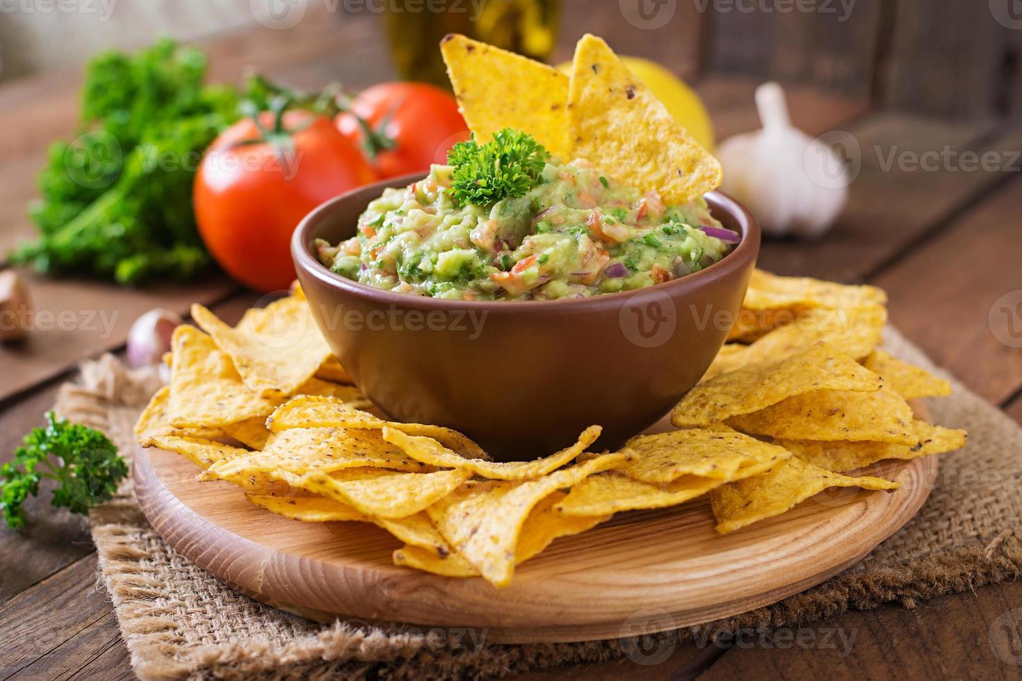 guacamole avocado, limoen, tomaat, ui en koriander, geserveerd met nacho's foto