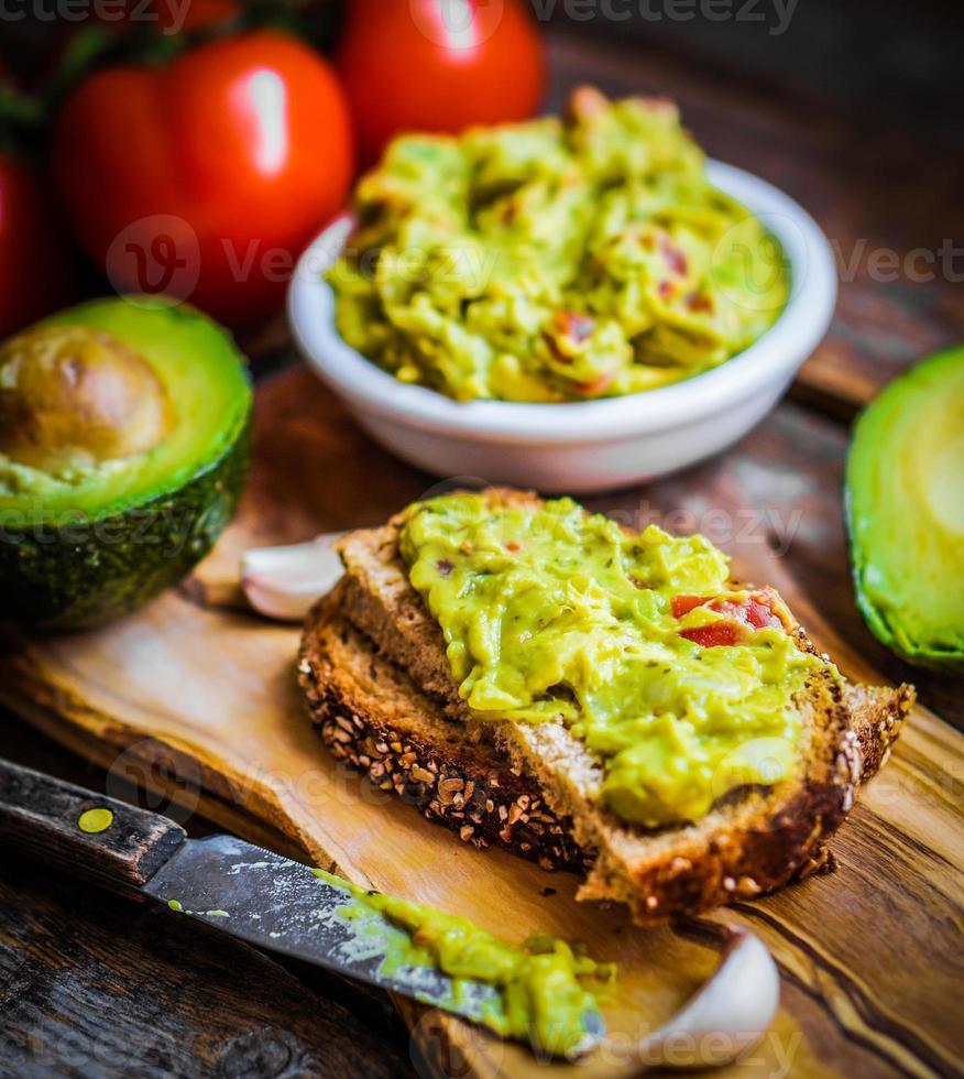 guacamaole met brood en avocado op rustieke houten achtergrond foto