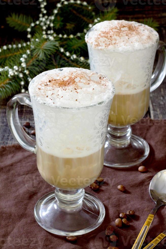 cappuccino met een versierde kerstboom op een houten tafel foto