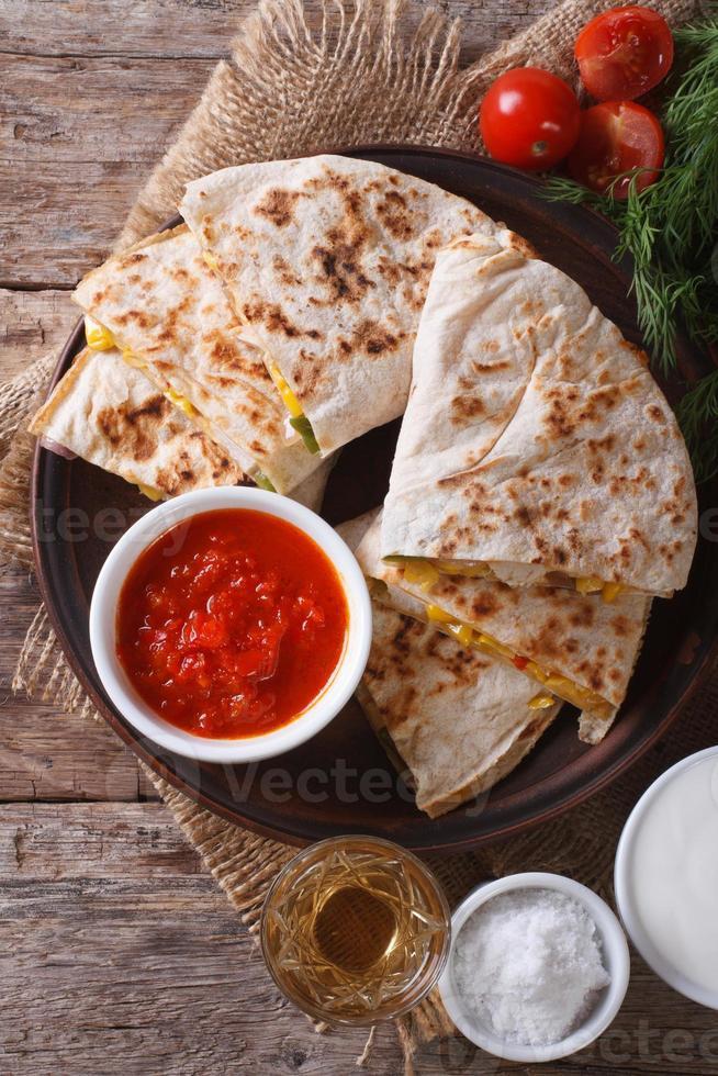quesadilla gesneden en sauzen op plaat close-up. verticaal foto