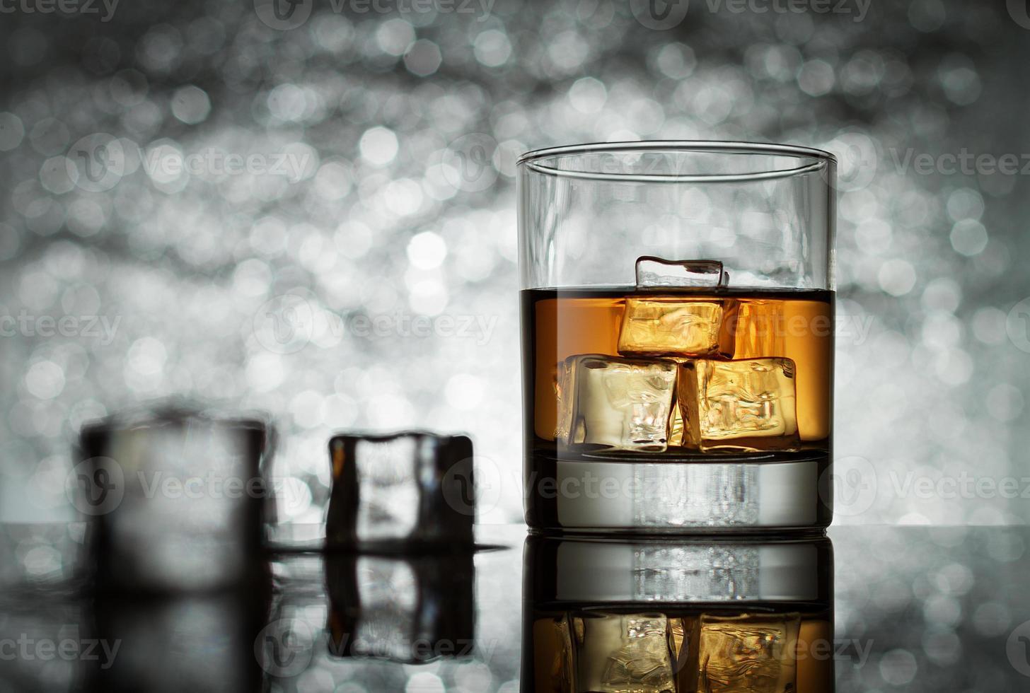 glas met ijsblokjes op abstracte achtergrond foto