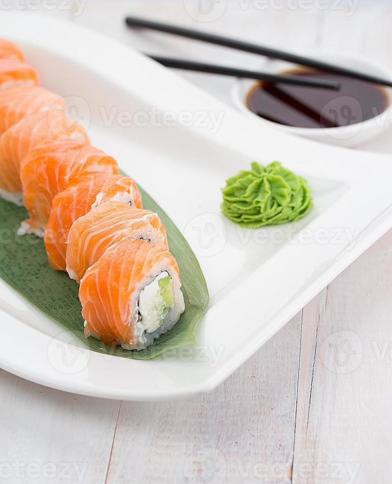 Zalm sushi roll op een witte plaat met wasabi foto