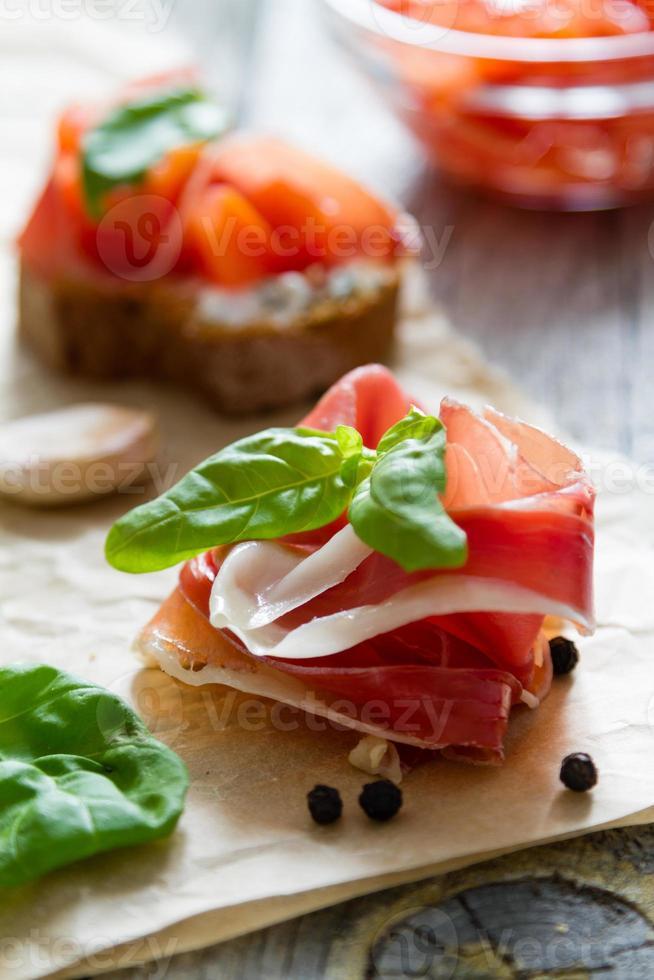 plakje vlees en tomatenbruschetta met basilicumblaadjes, knoflook foto