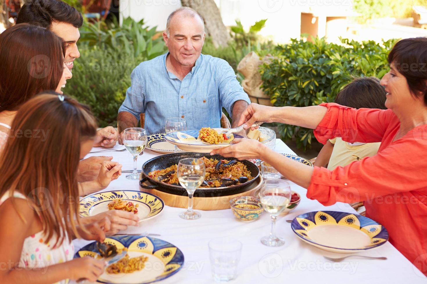 familie van meerdere generaties die samen van maaltijd op terras genieten foto