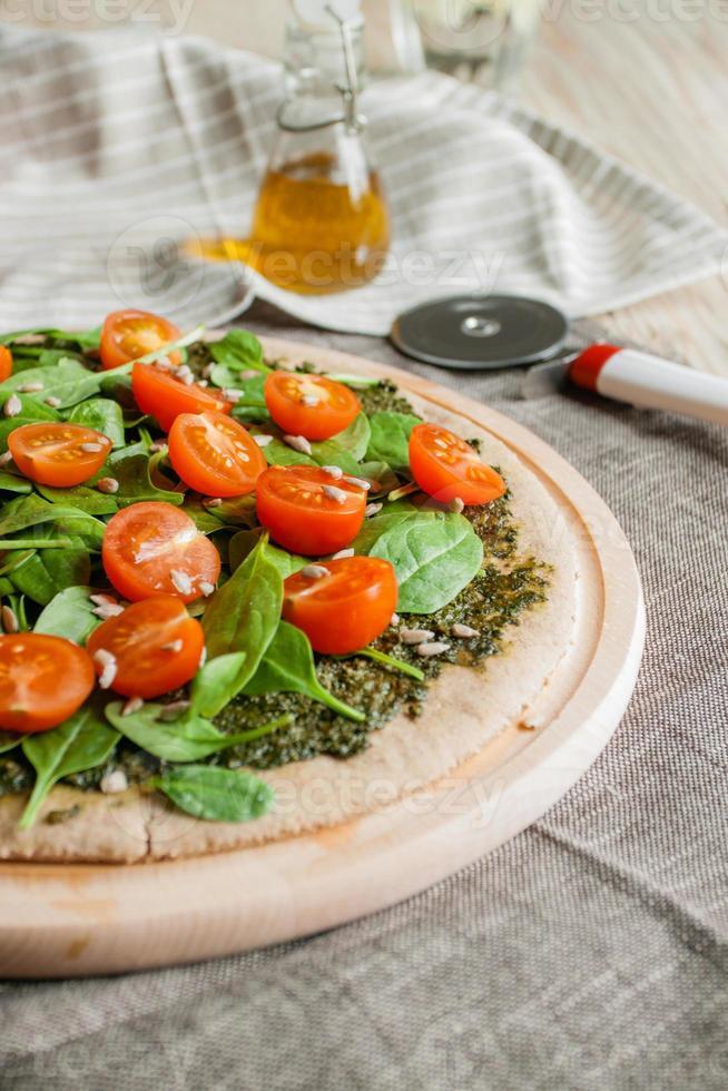 pizza met pesto, spinazie en kerstomaatjes foto