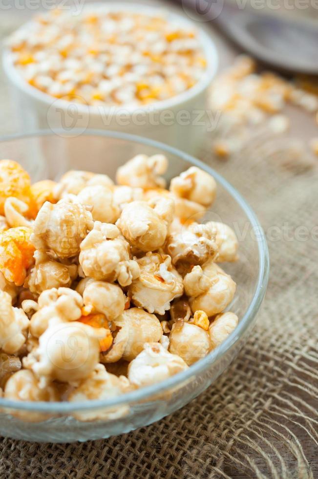 kom popcorn op een houten tafel, karamel popcorn foto