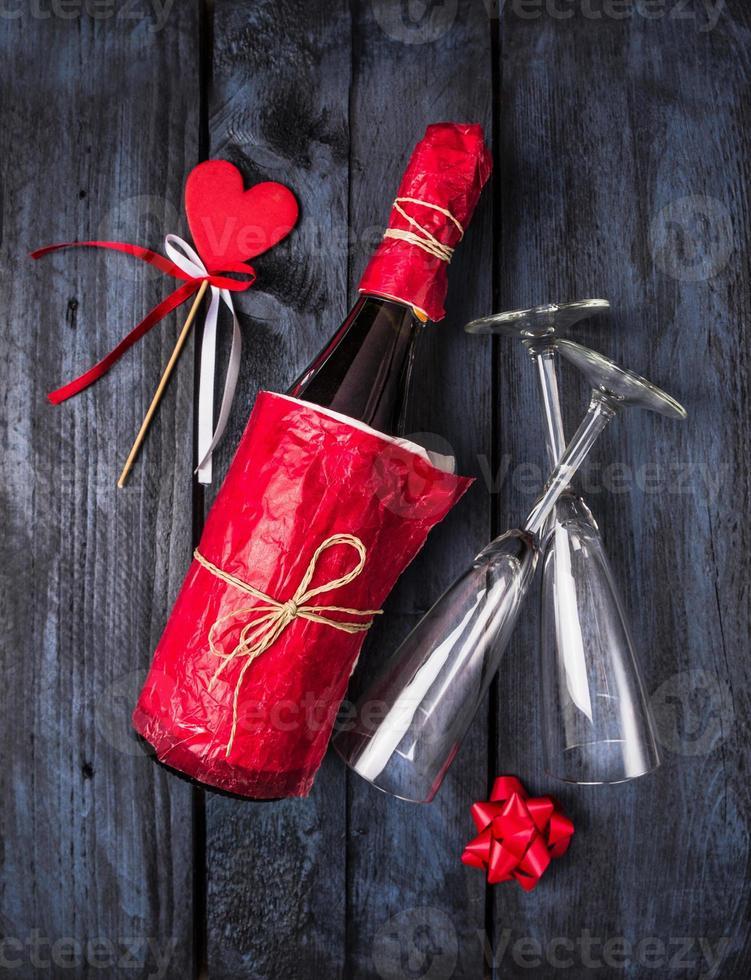 fles champagne in rood papier, hart op blauwe achtergrond foto