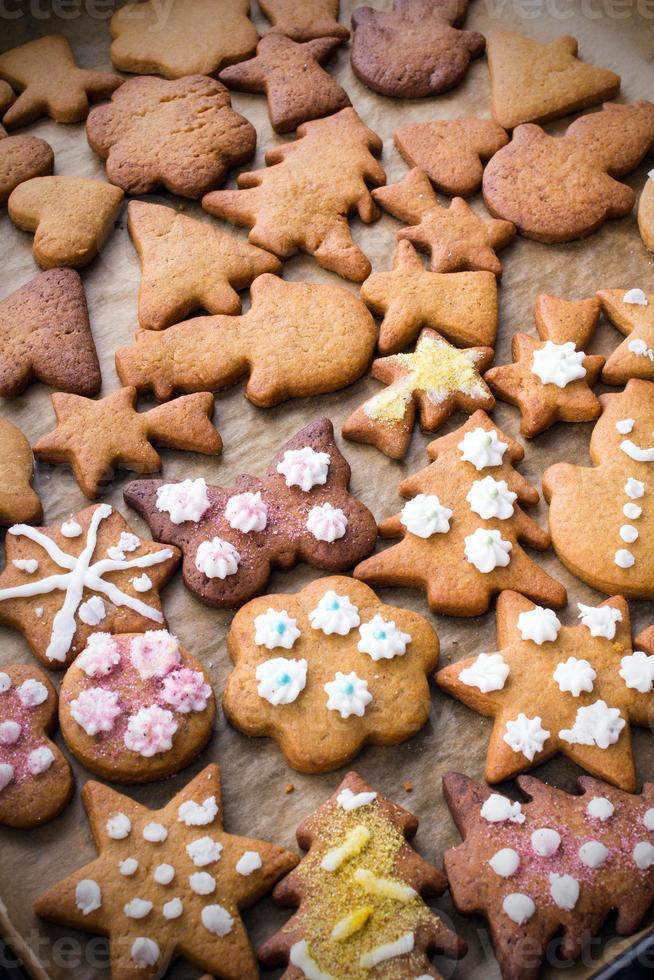kleurrijke peperkoek kerstkoekjes op bakpapier foto