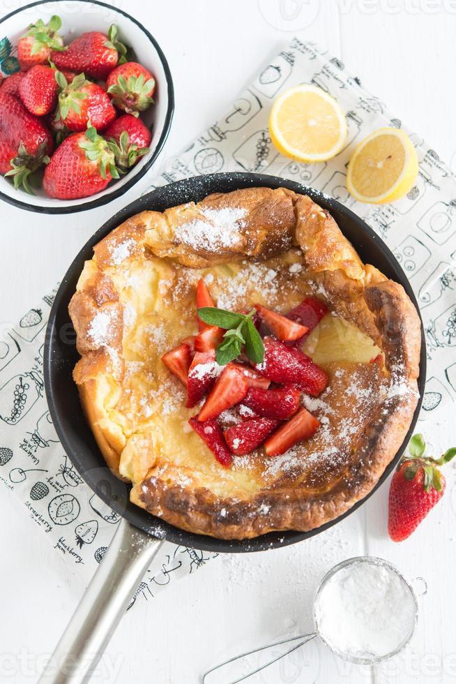 dutch baby (gebakken pannenkoek geserveerd met aardbeien) foto
