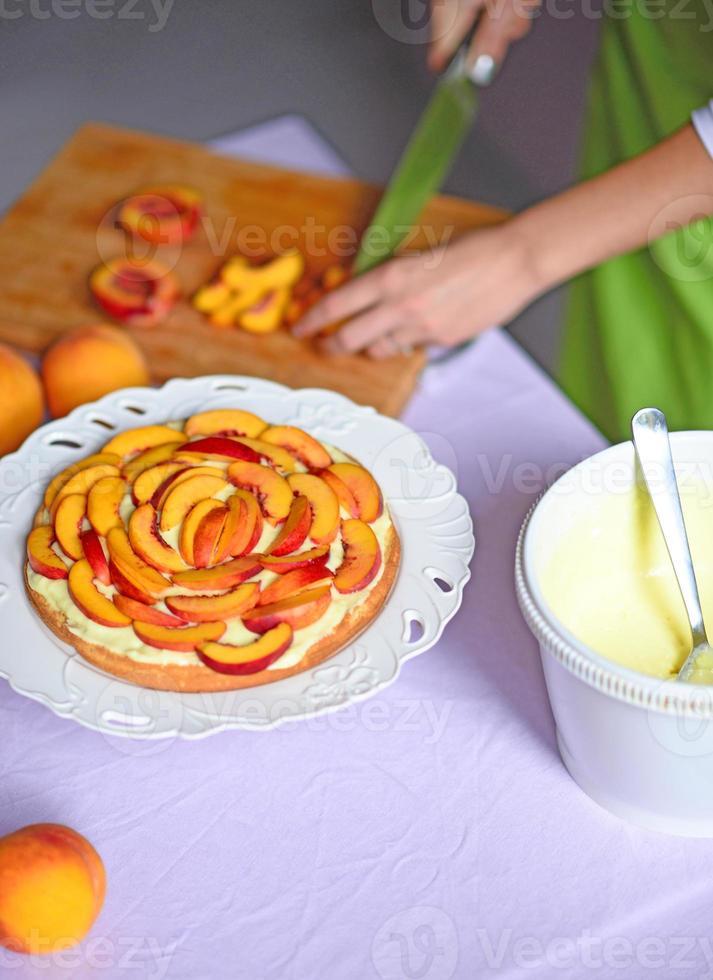 vrouw met de hand gesneden perzik voor cake foto