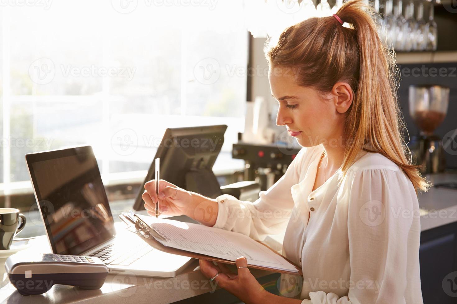 vrouwelijke restaurantmanager die bij balie werkt foto