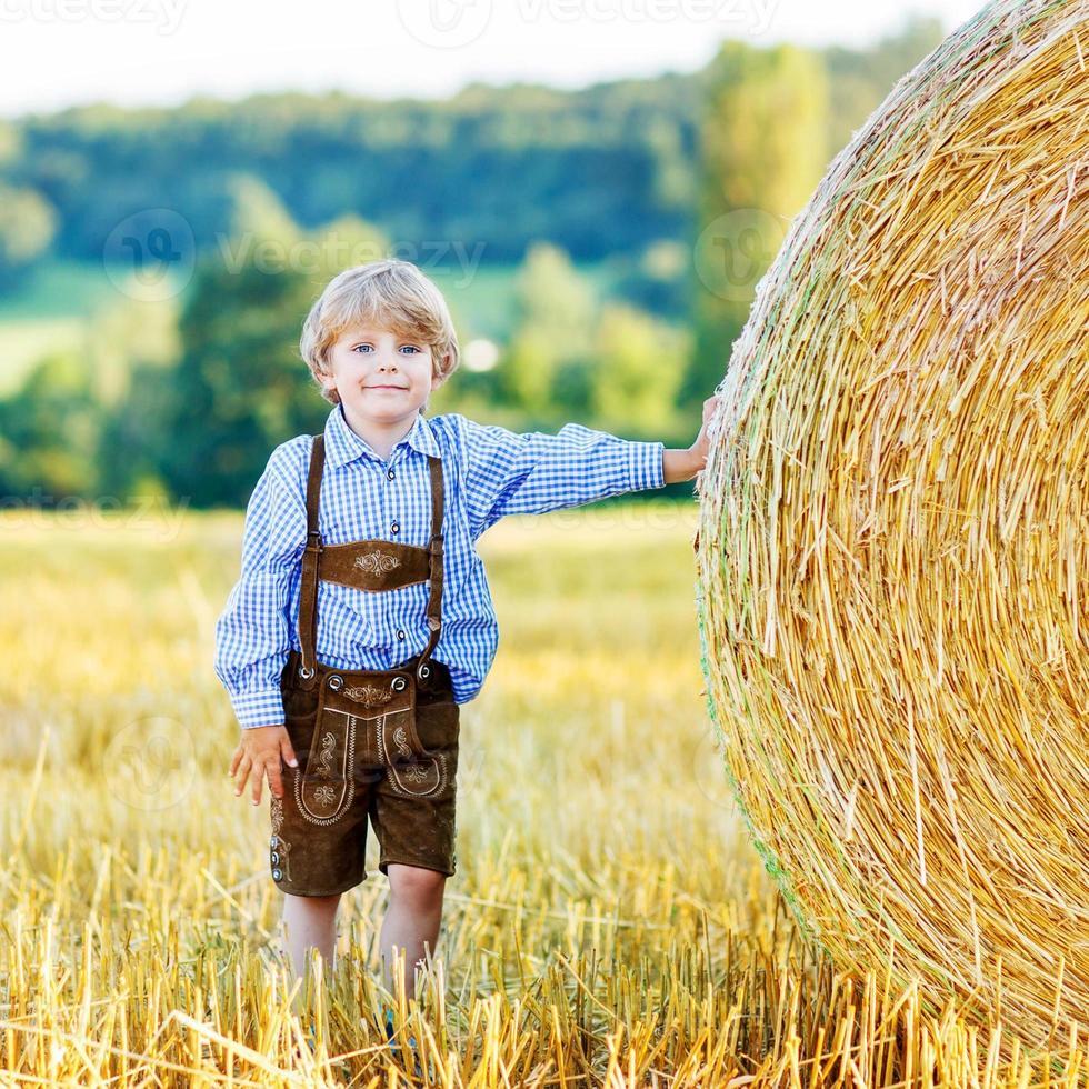 schattige kleine jongen jongen plezier met hooi stapel foto