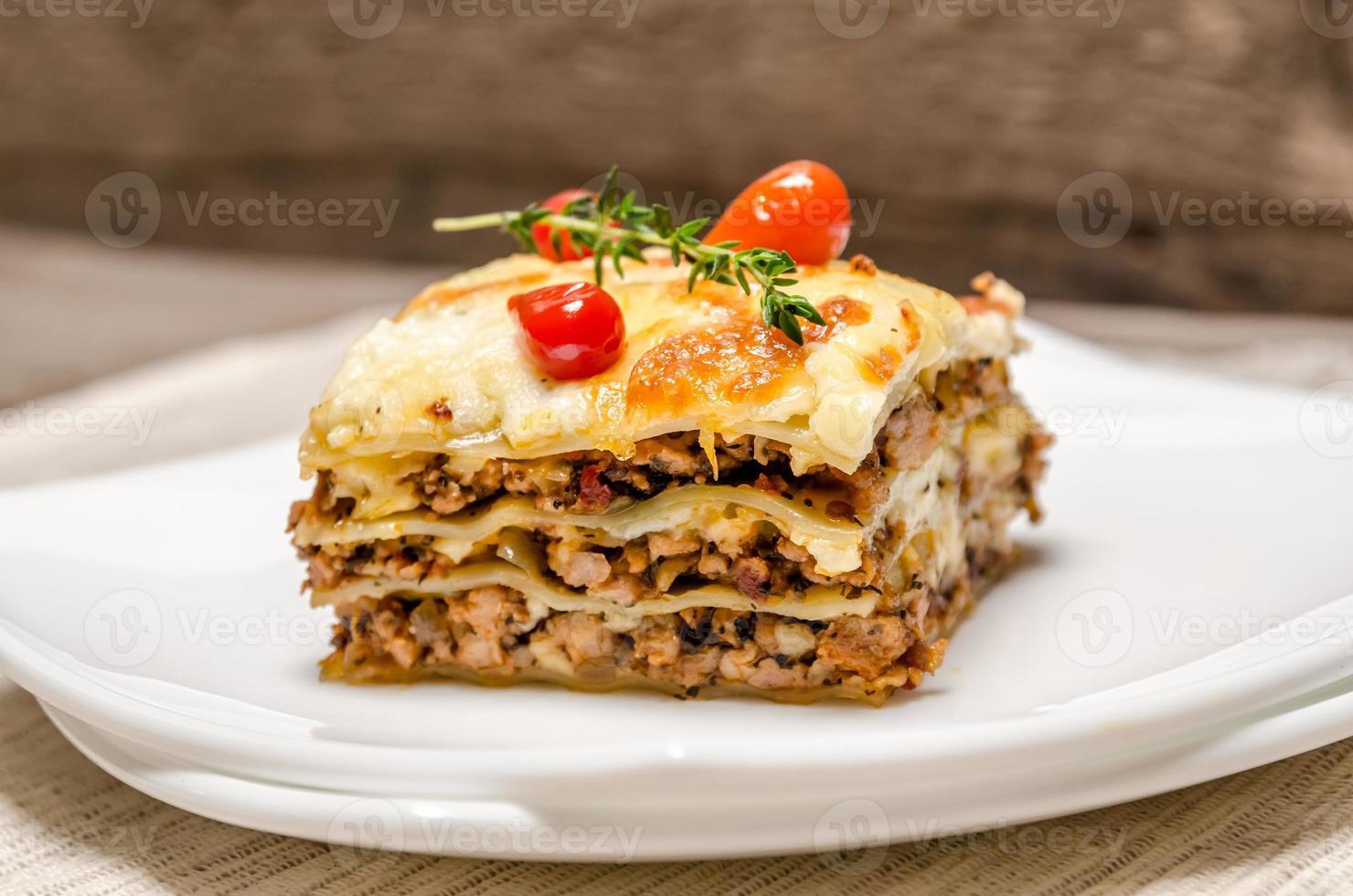 portie lasagne op het vierkante bord foto