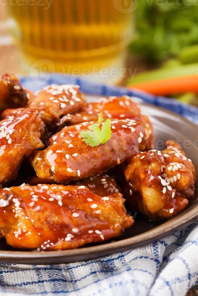 gebakken kippenvleugels in honingsaus bestrooid met sesamzaadjes. foto