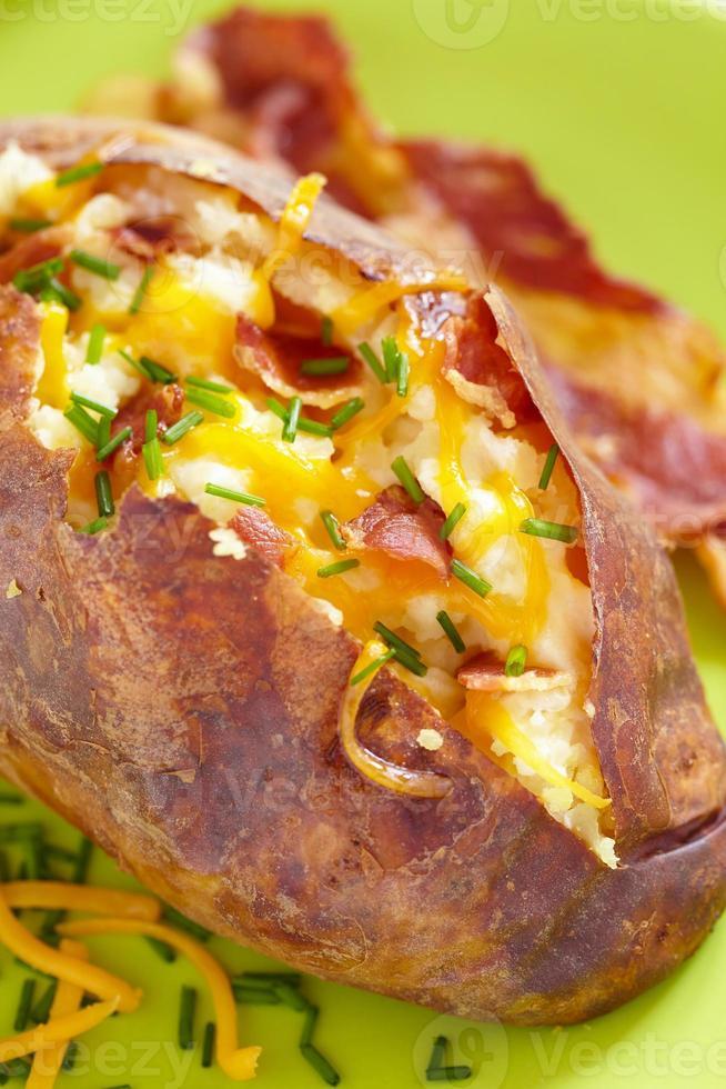 gebakken aardappel met spek, kaas en bieslook foto