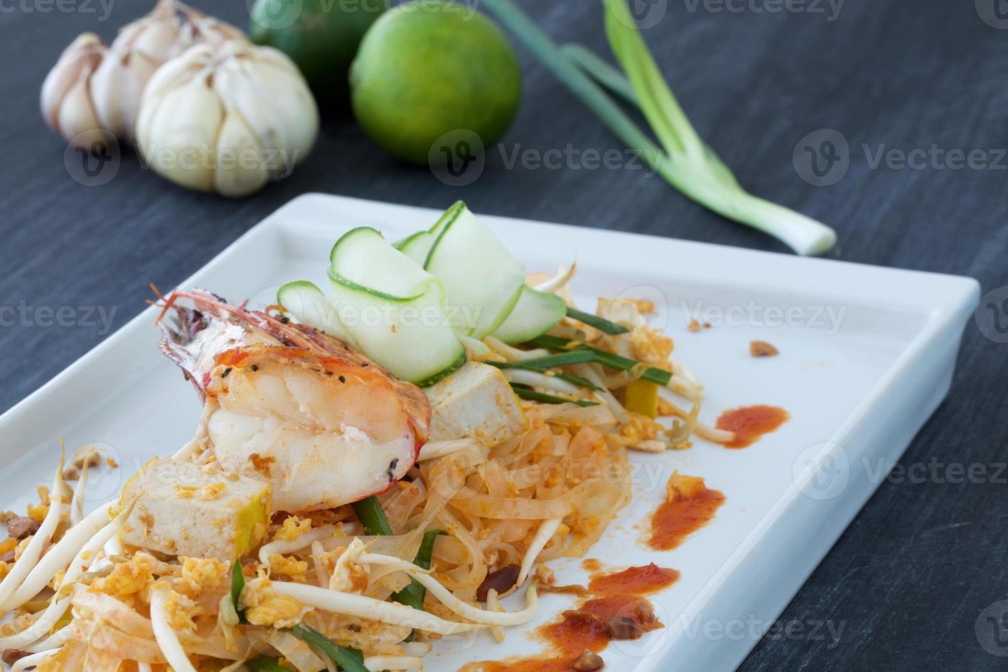 pad thai, garnalen en groente op plaat met ingrediënten rondom foto