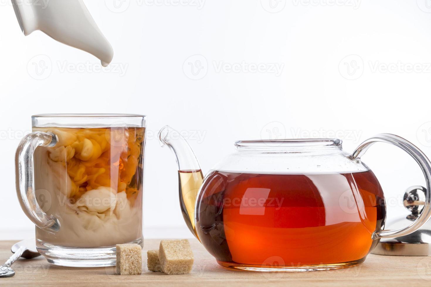 los melk op in een kopje zwarte thee. foto