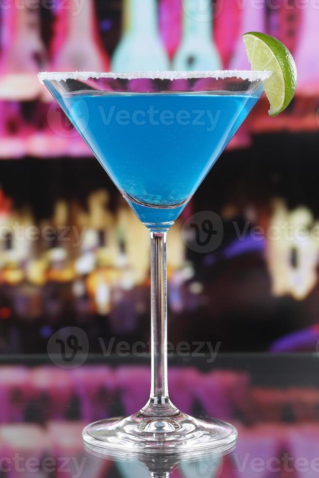 blauwe curacao cocktail in Martiniglas in een bar foto