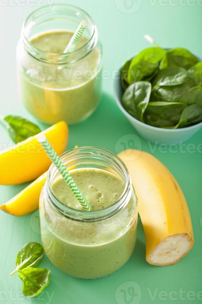 gezonde groene smoothie met spinazie mango banaan in glazen potten foto