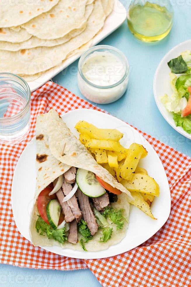 Griekse gyros met varkensvlees, groenten en huisgemaakt pitabroodje foto