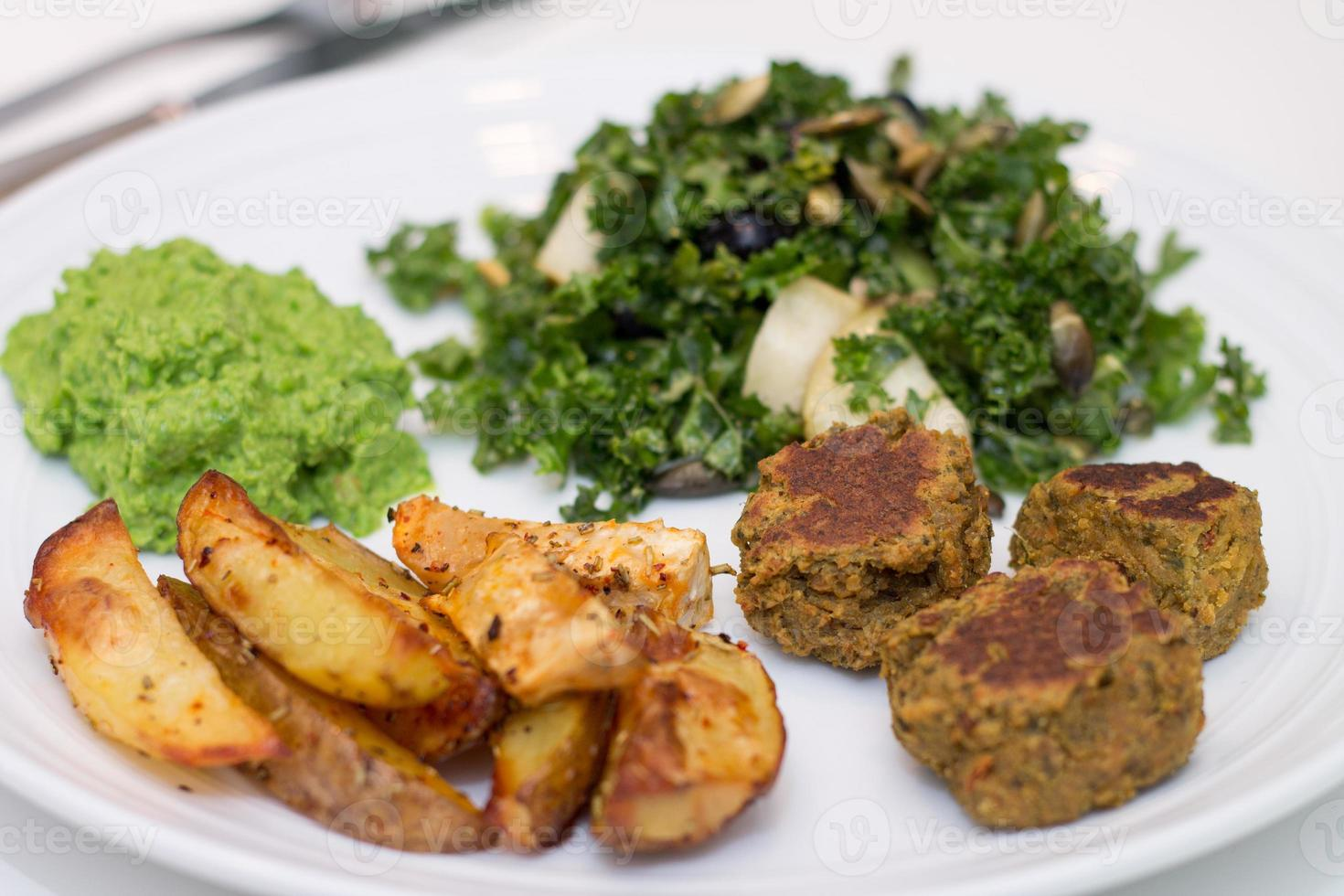 gebakken aardappelen, falafels, erwtenmousse en salade op witte plaat foto