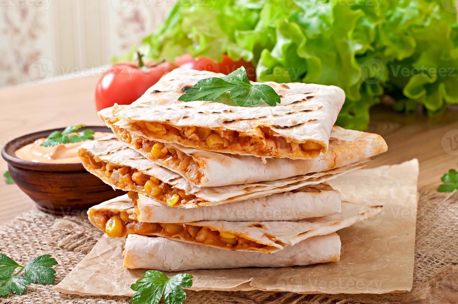 Mexicaanse quesadilla gesneden met groenten en sauzen foto