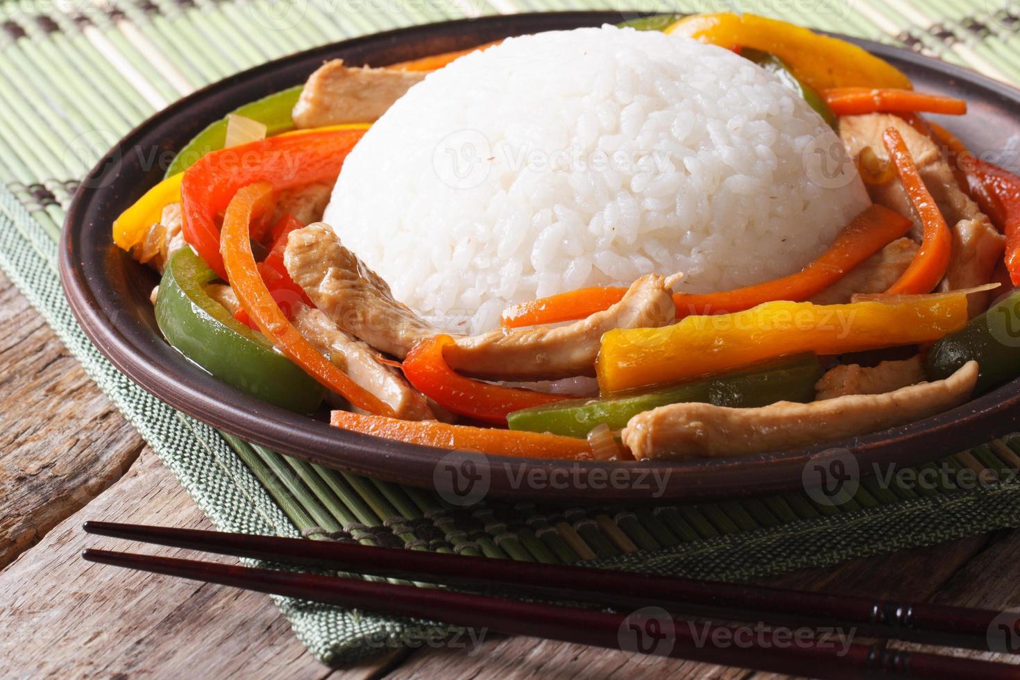 Chinese rijst met kip en groenten close-up op een plaat foto