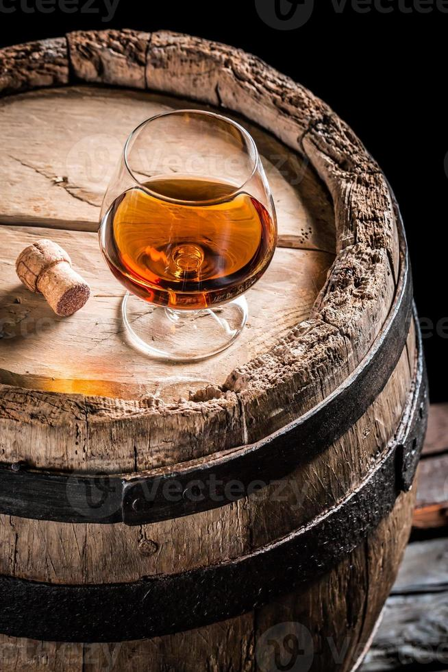 glas goede cognac in de kelder van de distilleerderij foto
