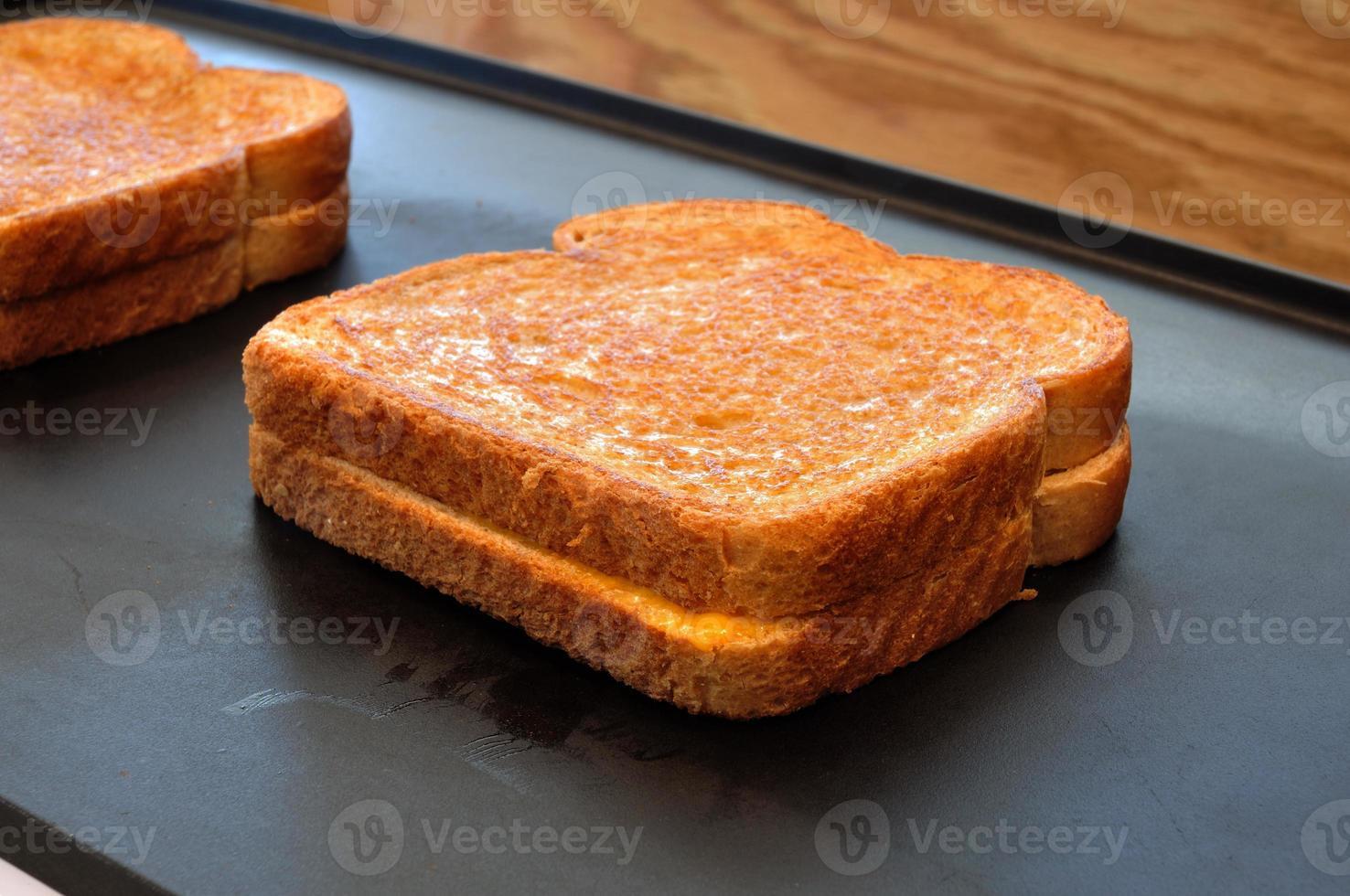 twee broodjes gegrilde kaas op een hete plaat foto