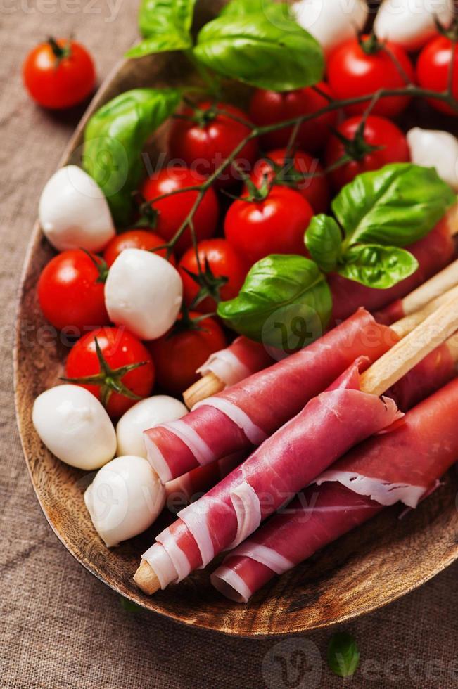 Italiaanse prosciutto met tomaat, mozzarella en basilicum foto