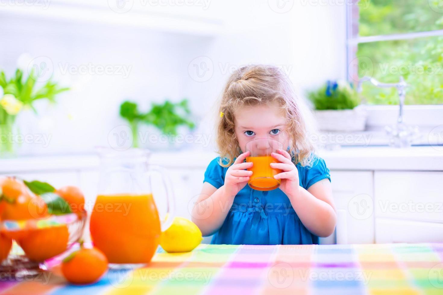 klein meisje drinken sinaasappelsap foto