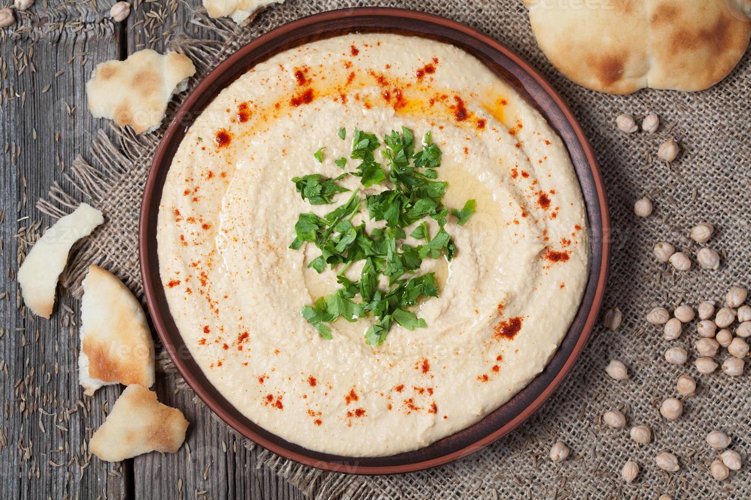 kom hummus, romig vegetarisch eten met kikkererwten, paprika foto