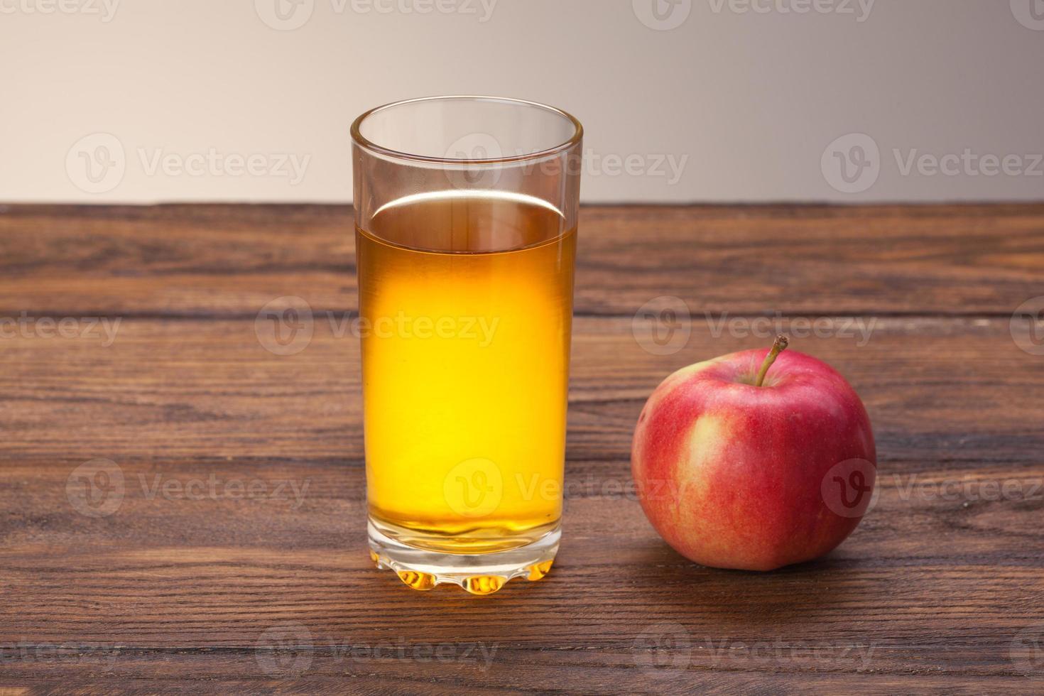 glas appelsap en rode appel op hout foto