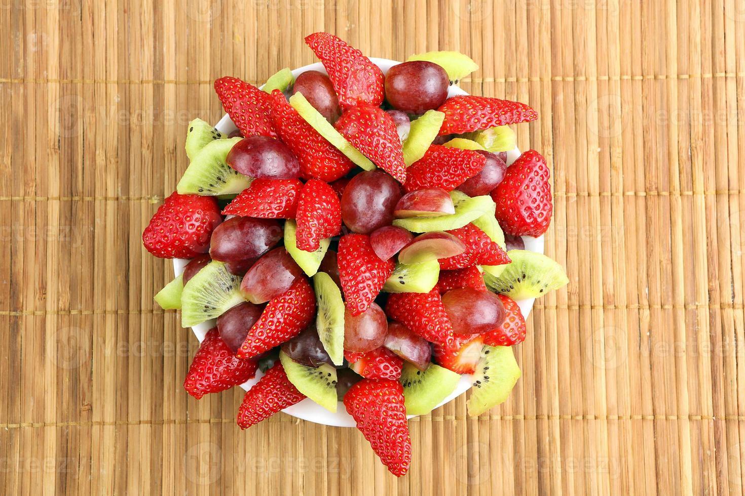 fruitsalade met aardbeien, druiven en kiwi op rotan backgro foto