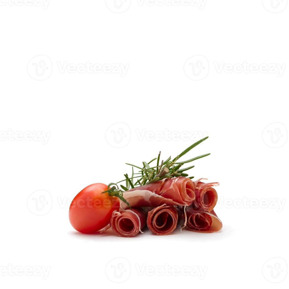 plakjes parmaham en cherrytomaat met rozemarijntak foto
