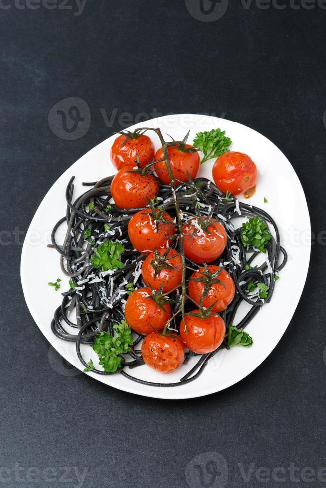 plaat van zwarte pasta met gebakken tomaten, Parmezaanse kaas foto