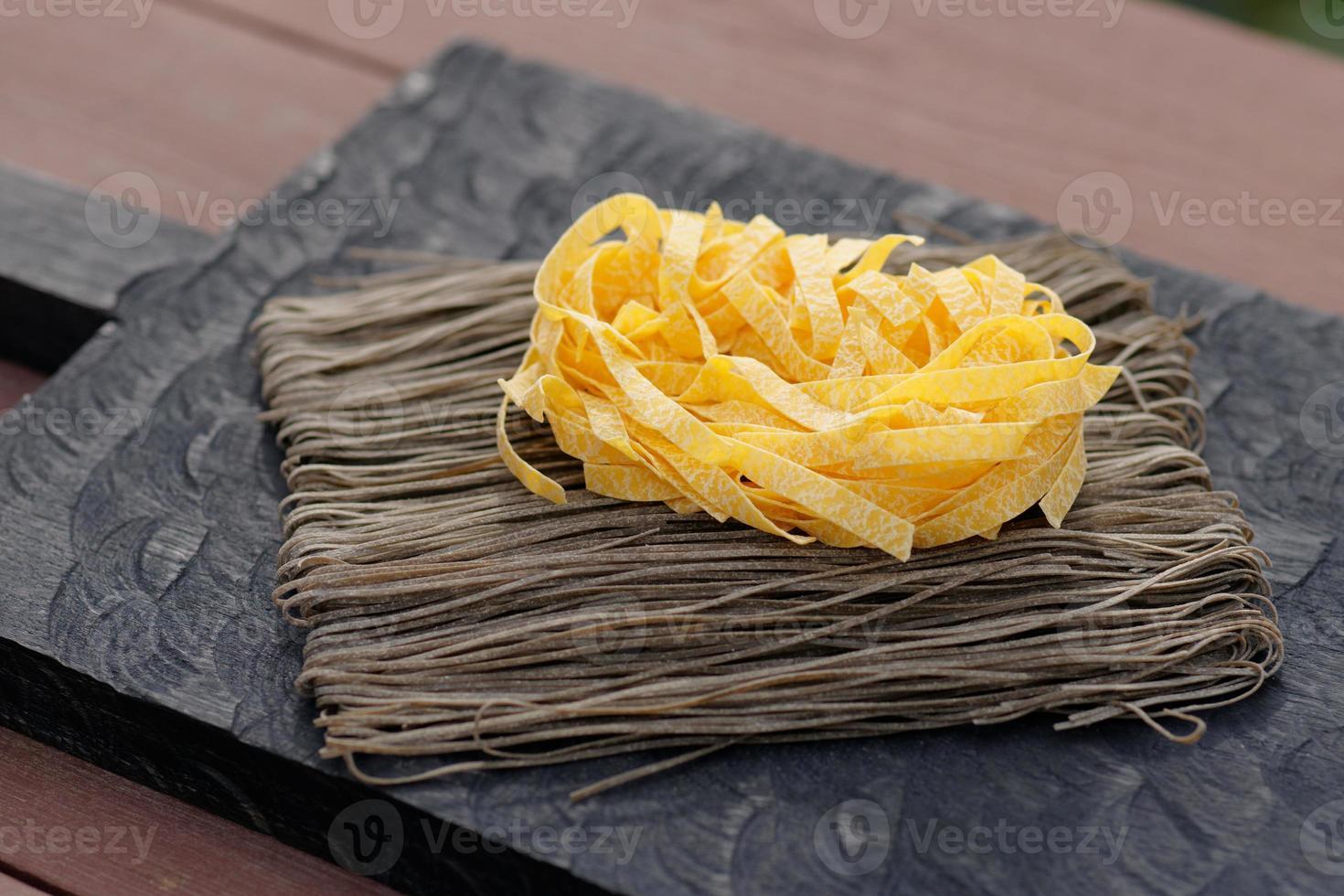 twee soorten pasta op houten plank foto