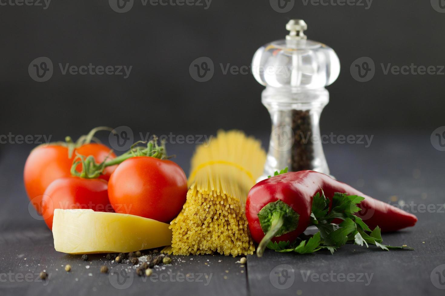 Italiaanse ingrediënten: spaghetti, kruiden, tomaten, Spaanse peper op houten achtergrond foto
