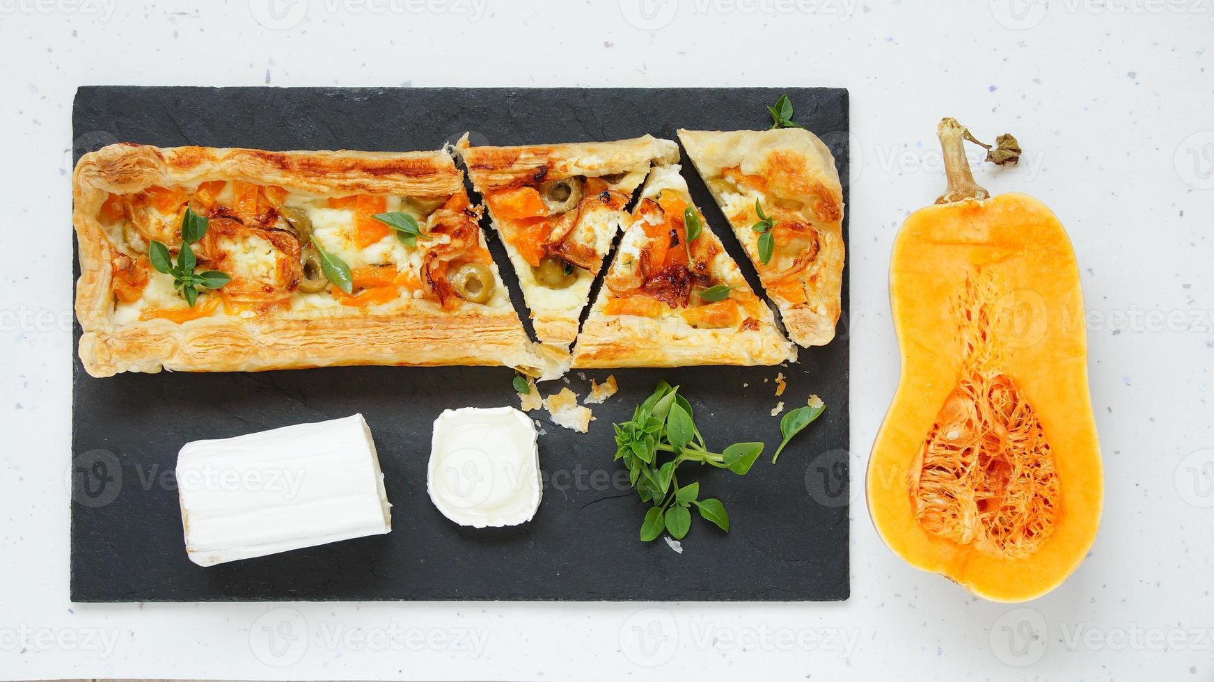 taart met pompoen, geitenkaas, olijven op het stenen bord foto
