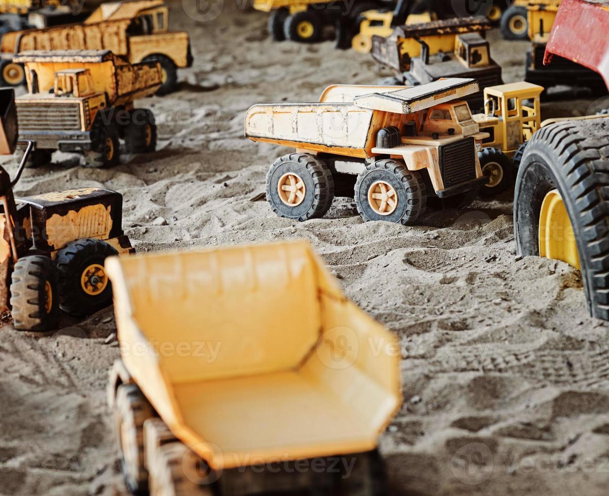 oud, verroest bouwspeelgoed in zandbak foto