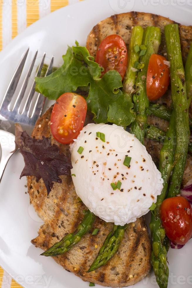 gepocheerd ei op geroosterd brood met asperges, tomaten en groenten foto