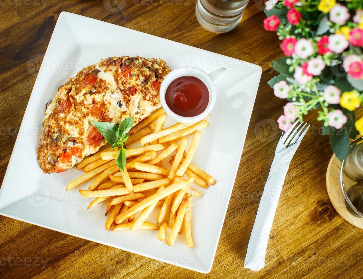 roerei en frietjes op een houten tafel foto